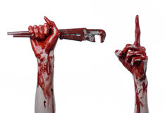 Blutige Hand, die einen justierbaren Schlüssel, blutigen Schlüssel, verrückter Klempner, blutiges Thema, Halloween-Thema, weißer  Lizenzfreies Stockbild