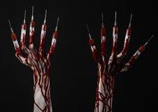 Blutige Hand mit Spritze auf den Fingern, Zehenspritzen, Handspritzen, schreckliche blutige Hand, Halloween-Thema, Zombiedoktor,  Lizenzfreies Stockbild