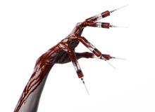 Blutige Hand mit Spritze auf den Fingern, Zehenspritzen, Handspritzen, schreckliche blutige Hand, Halloween-Thema, Zombiedoktor,  Stockfotografie