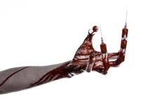 Blutige Hand mit Spritze auf den Fingern, Zehenspritzen, Handspritzen, schreckliche blutige Hand, Halloween-Thema, Zombiedoktor,  Stockbild