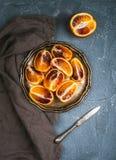 Blutige rote sizilianische Orangen schnitten in Viertel in der Weinlesemetallplatte über konkretem strukturiertem Hintergrund Stockfotografie