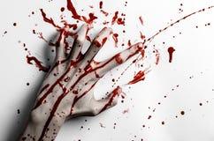 Blutiges Halloween-Thema: blutiger Handdruck auf einem Weiß verlässt blutige Wand Stockbilder