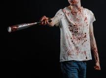 Blutiges Thema: Der Kerl in einem blutigen T-Shirt, das einen blutigen Schläger auf einem schwarzen Hintergrund hält Lizenzfreies Stockbild
