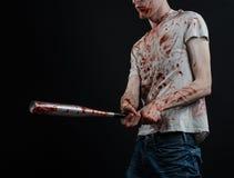 Blutiges Thema: Der Kerl in einem blutigen T-Shirt, das einen blutigen Schläger auf einem schwarzen Hintergrund hält Stockfotografie