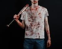 Blutiges Thema: Der Kerl in einem blutigen T-Shirt, das einen blutigen Schläger auf einem schwarzen Hintergrund hält Stockbilder