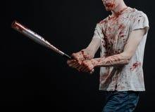 Blutiges Thema: Der Kerl in einem blutigen T-Shirt, das einen blutigen Schläger auf einem schwarzen Hintergrund hält Stockfoto