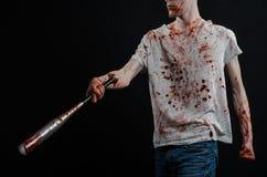 Blutiges Thema: Der Kerl in einem blutigen T-Shirt, das einen blutigen Schläger auf einem schwarzen Hintergrund hält Stockbild