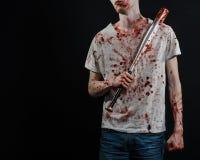 Blutiges Thema: Der Kerl in einem blutigen T-Shirt, das einen blutigen Schläger auf einem schwarzen Hintergrund hält Stockfotos