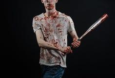 Blutiges Thema: Der Kerl in einem blutigen T-Shirt, das einen blutigen Schläger auf einem schwarzen Hintergrund hält Lizenzfreies Stockfoto