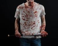 Blutiges Thema: Der Kerl in einem blutigen T-Shirt, das einen blutigen Schläger auf einem schwarzen Hintergrund hält Lizenzfreie Stockbilder