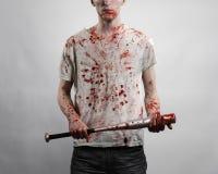 Blutiges Thema: Der Kerl in einem blutigen T-Shirt, das einen blutigen Schläger auf einem weißen Hintergrund hält Lizenzfreie Stockbilder