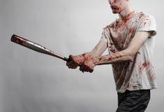 Blutiges Thema: Der Kerl in einem blutigen T-Shirt, das einen blutigen Schläger auf einem weißen Hintergrund hält Lizenzfreie Stockfotos