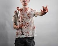 Blutiges Thema: Der Kerl in einem blutigen T-Shirt, das einen blutigen Schläger auf einem weißen Hintergrund hält Lizenzfreies Stockfoto