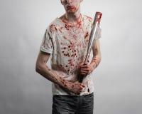 Blutiges Thema: Der Kerl in einem blutigen T-Shirt, das einen blutigen Schläger auf einem weißen Hintergrund hält Lizenzfreie Stockfotografie