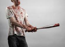 Blutiges Thema: Der Kerl in einem blutigen T-Shirt, das einen blutigen Schläger auf einem weißen Hintergrund hält Stockfoto