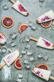Blutorange-, Jogurt- und Granolaeis am stiel auf Eis, grauer Hintergrund lizenzfreie stockbilder