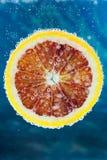 Blutorangescheibe, die in Wasser fällt Stockfoto