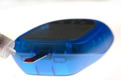 Bluttropfen auf Diabetesmeßinstrument mit Insulinspritze lizenzfreies stockfoto