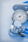 Bluud pressure monitor and stethoscope on blue Stock Photo
