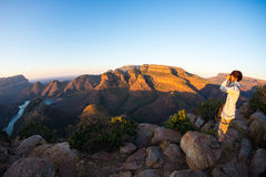 Blyde River Canyon, famous travel destination in South Africa. Tourist looking at panorama with binocular. Last sunlight on the mo Stock Images