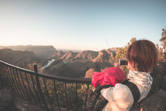 Blyde River Canyon, famous travel destination in South Africa. Tourist taking photo with smartphone at sunset from the terrace abo Royalty Free Stock Photos