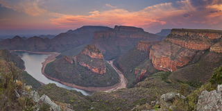 Blyde River Canyon in South Africa at sunset. View over the Blyde River Canyon and the Three Rondavels in South Africa at sunset Royalty Free Stock Photos