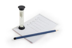 Blyertspenna, anteckningsbok och timglas Royaltyfria Bilder