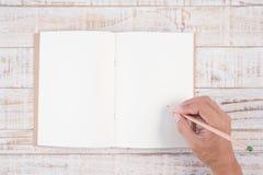 Blyertspenna för manhandinnehav och handstilanteckningsbok på den wood tabellen för Royaltyfria Bilder