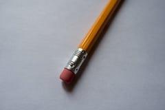 Blyertspenna med radering av gummi som ligger på vitbok Fotografering för Bildbyråer