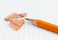 Blyertspenna med shavings på ett pappers- ark arkivfoto