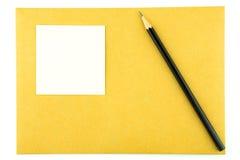 Blyertspenna och anteckningsbok på kuvert Royaltyfria Bilder