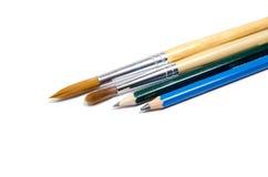 Blyertspenna och målarpensel arkivbild