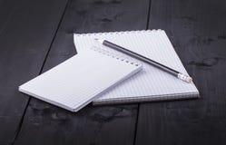 Blyertspenna och notepad med spiral på svart trä Arkivfoto