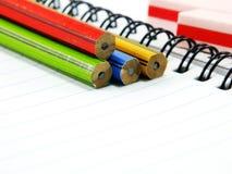 Blyertspenna och radergummi på anteckningsbokpapper Arkivfoton