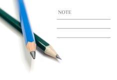 Blyertspenna och text Arkivfoton