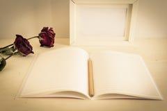 Blyertspenna på öppnat anteckningsbokpapper med torra rosor och rambilden Fotografering för Bildbyråer