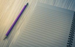 Blyertspenna på den kontrollerade anteckningsboken på wood bakgrund Royaltyfri Fotografi