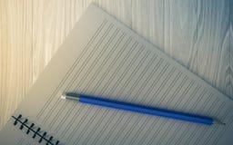 Blyertspenna på den kontrollerade anteckningsboken på wood bakgrund Royaltyfria Bilder
