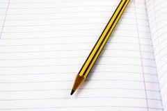 Blyertspenna på en vit sida Fotografering för Bildbyråer