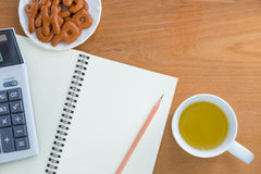 Blyertspenna, räknemaskin, anteckningsbok, mellanmål och drink arkivbild