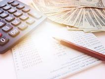 Blyertspenna, räknemaskin, pengar och sparkontobankbok eller bokföringsunderlag på vit bakgrund Arkivbilder
