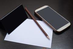 Blyertspenna som förläggas på vitbok och smartphonen royaltyfri bild