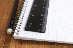 Blyertspenna, spiralanteckningsbok och linjal Arkivbild