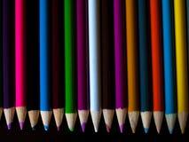 Blyertspennafärgpennor som ligger på en tabell Royaltyfri Bild