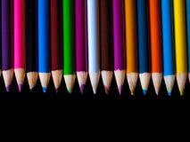 Blyertspennafärgpennor som ligger på en tabell Royaltyfria Foton