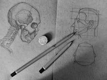 Blyertspennan skissar av en skalle och ett mänskligt huvud i den gamla anteckningsboken royaltyfri fotografi
