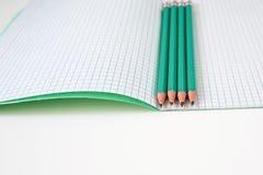 Blyertspennor bredvid skolaanteckningsboken royaltyfria bilder