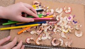 Blyertspennor för handinnehavfärg över en anteckningsbok Royaltyfri Foto