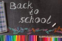 Blyertspennor, gem, anteckningsbok och titeln tillbaka till skolan som är skriftlig vid vit krita på den svarta svart tavlan för  Arkivbild
