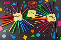 Blyertspennor i cirklar och titel tillbaka till skolan som är skriftlig på de gula styckena av papper på den svarta svart tavlan  Arkivfoton